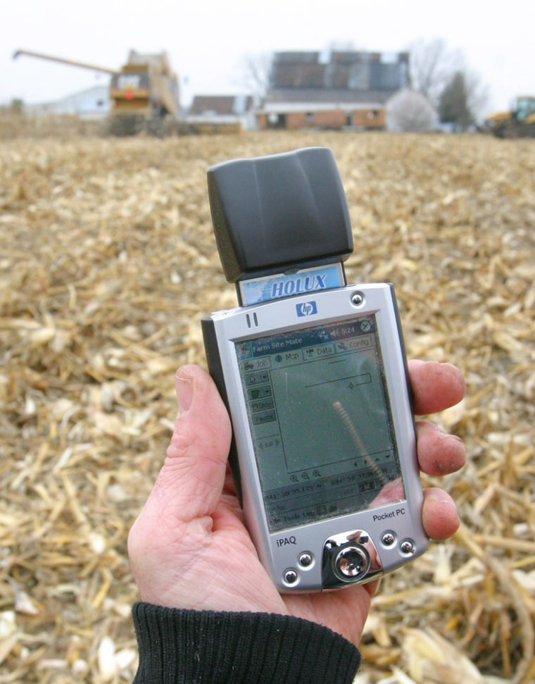Farmer Brian Watkins holds a Pocket PC with a GPS receiver out in one of his Kenton, Ohio fields. He uses the device to create maps to record different seed and fertilizer combinations in the fields.