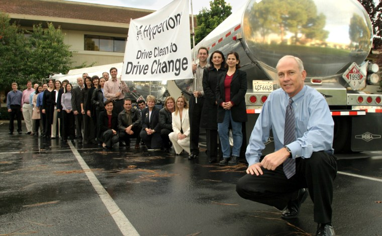 Hyperion CEO Godfrey Sullivan, right, poses with 25 employees and agasoline truck to make the point thata double-tanker full of gasoline will be saved in one year by the participation of just 25 employees in its clean car program.
