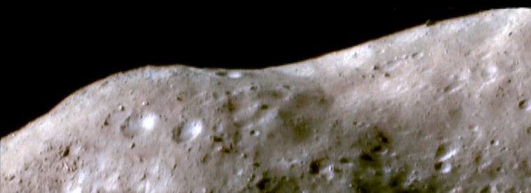 This false-color image of the asteroid Eros was taken by the NEAR Shoemaker spacecraft in October 2000 as it orbited 34 miles (54 kilometers) above the surface. In pale brown areas, the surface is thought to have been reddened and darkened by the solar wind and micrometeorite impacts. In white or blue areas, fresher materials are exposed from the subsurface on steep slopes.