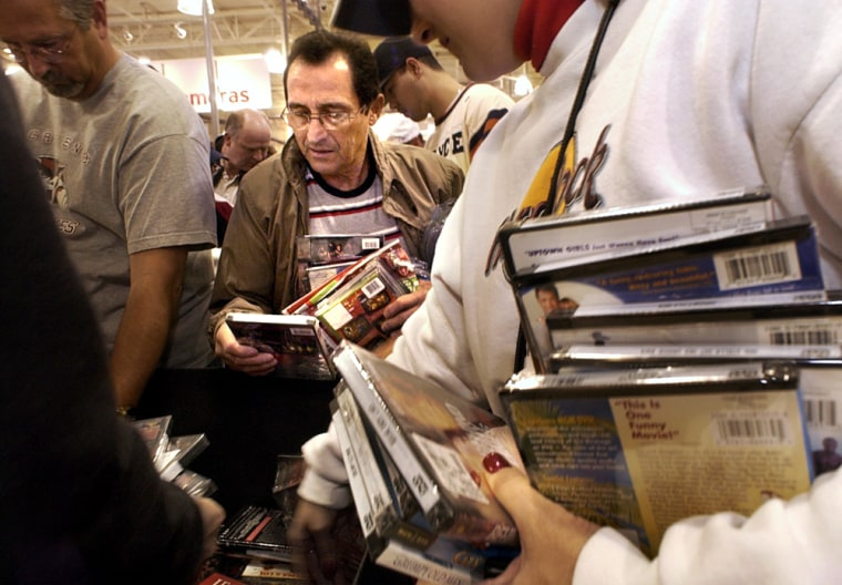 Joe Carrasco, center, and other bargain-hunters look through a bin of DVDs that were discounted to $4.99 at the Circuit City store in Elk Grove, Calif. on Friday morning.