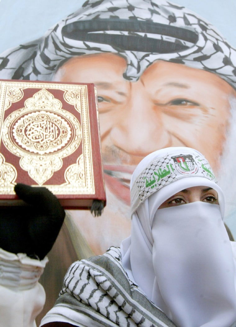 Palestinian woman supporter of Fatah movement holds a copy of the Koran in front of a poster of late Palestinian leader Arafat in nablus