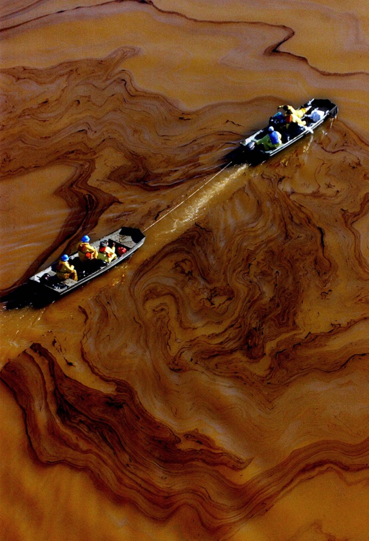 Workers pass through black oil on the Delaware River on Monday.