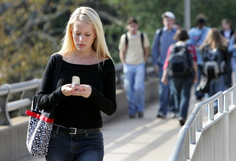 Christina Rainie, 19, left, checks her cell phone as she and other students make their way between classes at the University of Georgia in Athens, Ga.