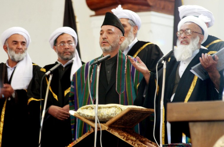 Afghan President Hamid Karzai, center, stands next to Chief Justice Fazl Hadi Shinwari, right, as he takes the oath of office during a ceremony at the Presidential Palace in Kabul, onTuesday.