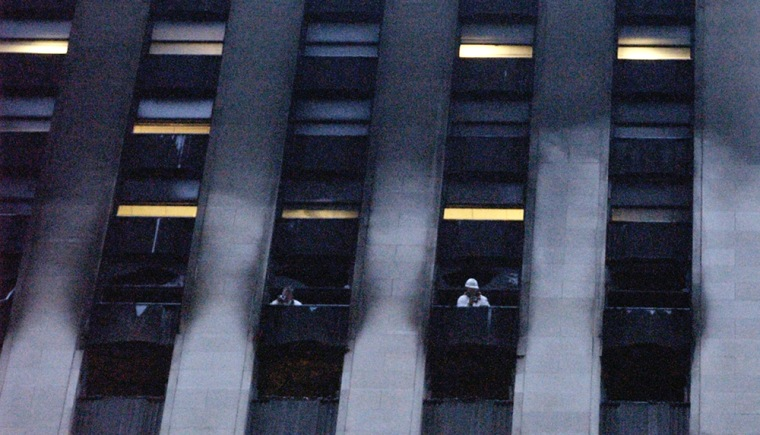 Investigators are seen taking photos from the windows of the LaSalle Bank building in Chicago late Tuesday.