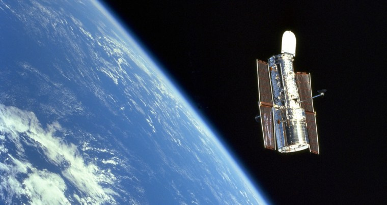 The Hubble Space Telescope floats above Earth after its release from the shuttle Discovery, at the end of a successful servicing mission in 1999.