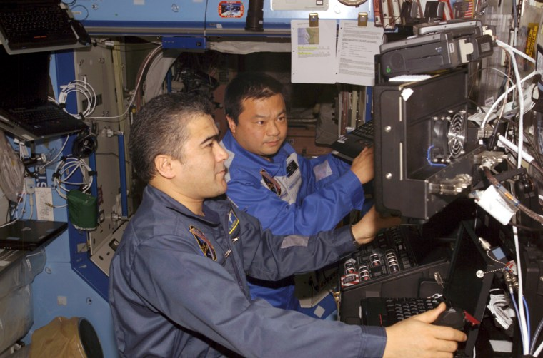 Kyrgyz-Russian cosmonaut Salizhan Sharipov and NASA astronaut Leroy Chiao conduct atraining exercise in the international space station'sDestiny laboratory module. Sharipov and Chiao have been told to reduce their caloric intake, at least until a supply ship arrives with more food.