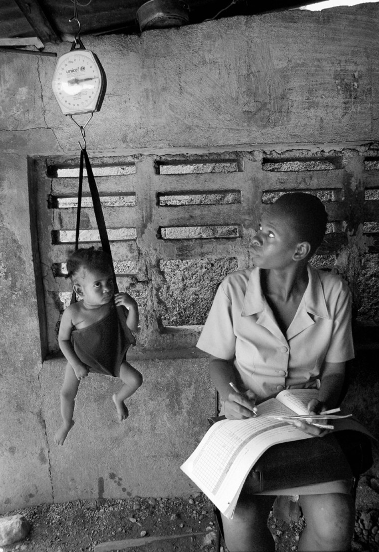 A toddler is weighed in a sling-scale by a heath worker from the UNICEF-assisted Martissant Community Clinicin Port-au-Prince, Haiti, in March 2004.