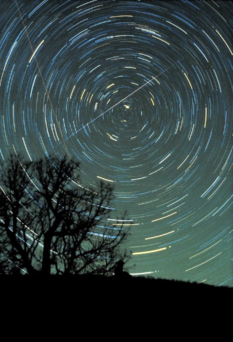 A Geminid meteor streaks across the night sky, with circular star trails whirling the background, in a time-exposure photo made by astronomer Jimmy Westlake in December 1985.