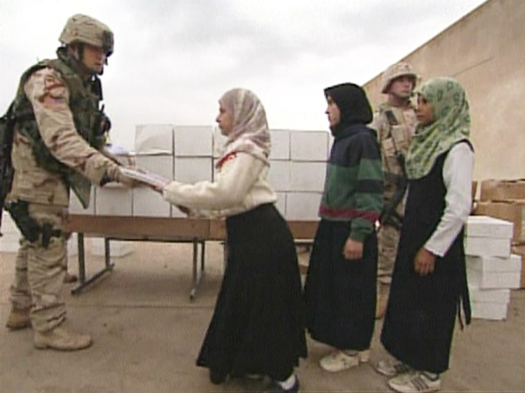 A soldier from 403rd civil affairs battalion hands out school supply kits to students of a primary school in central Iraq.