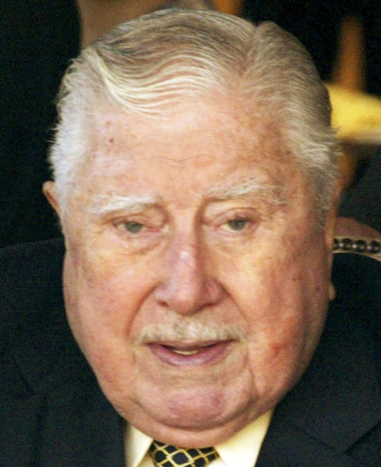 Former Chilean dictator Pinochet gets help from his bodyguards as he sits down in this file picture