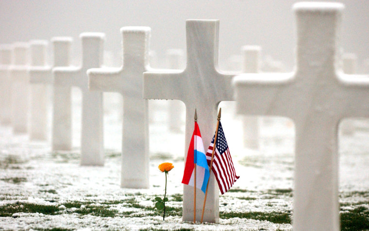Luxembourg and U.S. flags grace the grave of an American during a memorial of the Battle of the Bulge on Thursday in Hamm, Luxembourg.