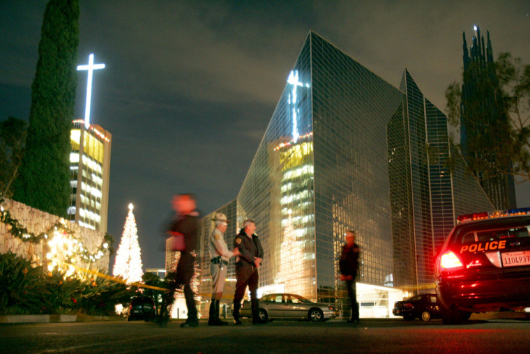 Law enforcement personnel block the entrance to the Crystal Cathedral complex after Thursday's shooting.