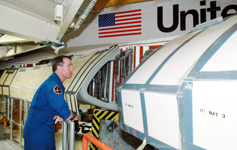 A crew member for the next shuttle mission,Stephen Robinson, looks inside the wing of theshuttle Discovery, which is in the Orbiter Processing Facility at NASA's Kennedy Space Center for launch processing. Discovery is scheduled for launchno earlier thanMay 12.