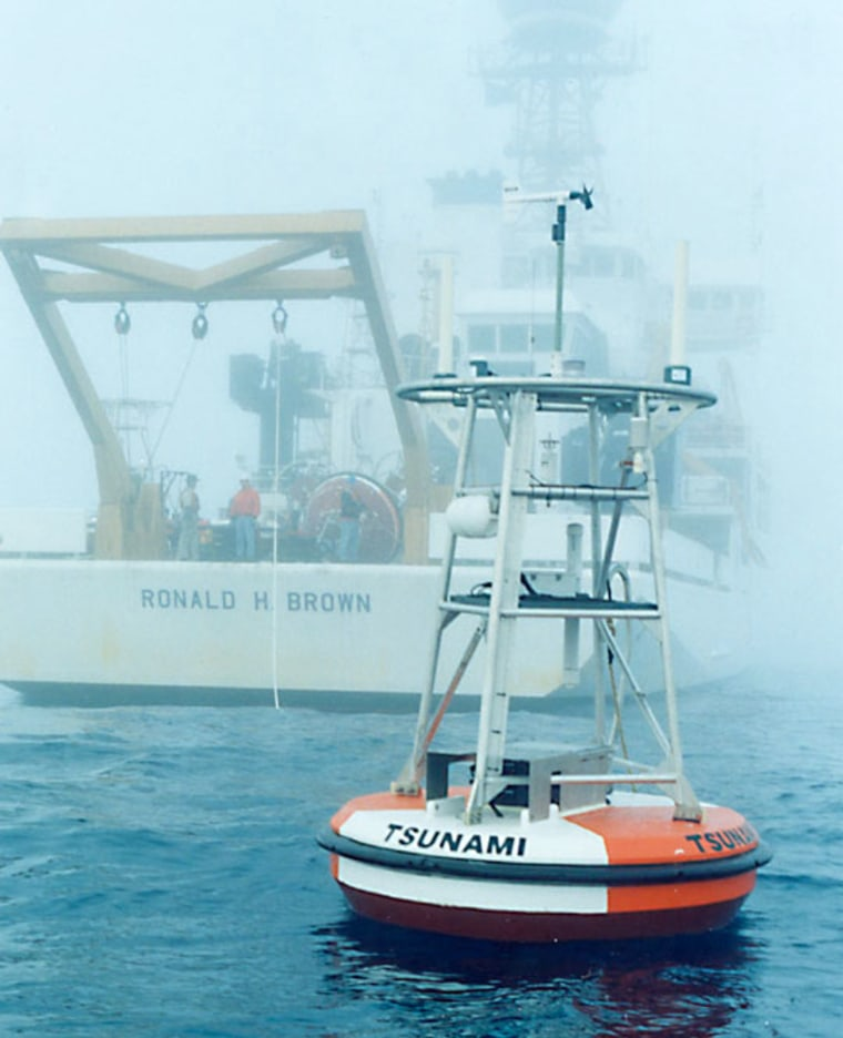 An ocean buoy deployed by the National Oceanic and Atmospheric Administration relays data from the seafloor of the PacificOcean to satellites in the sky as part of the U.S. tsunami monitoring network. The NOAA ship Ronald H. Brown floatsamid the background mist.
