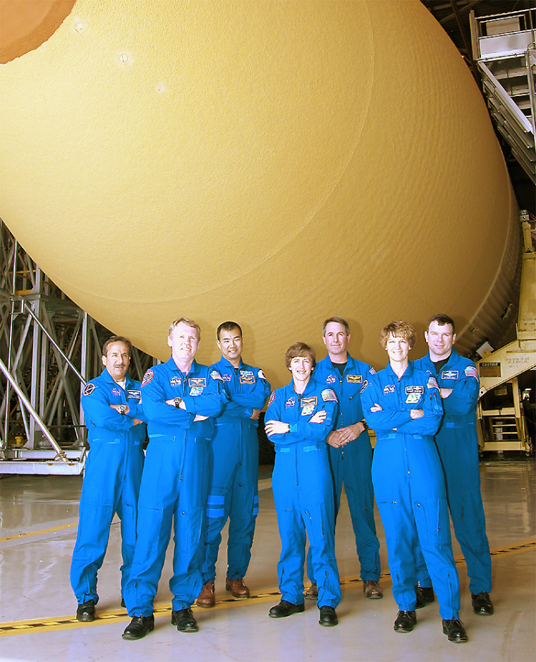 The crew of the next space shuttle mission stands beneath the redesigned fuel tank for their flight. From left are Charles Camarda, Andrew Thomas, Soichi Noguchi, Wendy Lawrence, Stephen Robinson, commander Eileen Collins and pilot James Kelly.