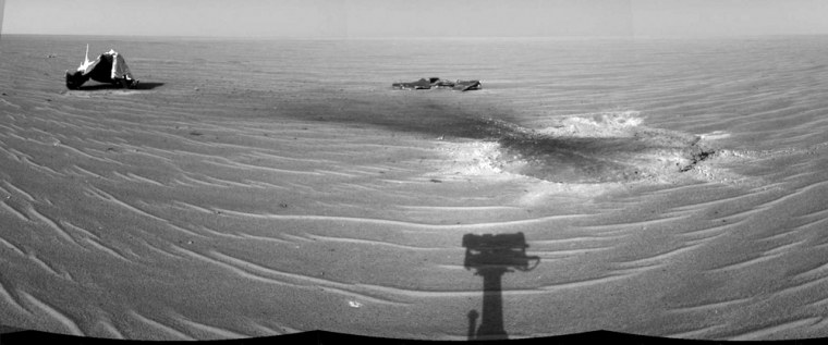 A panorama created from three separate images shows the shadow of the Opportunity rover's observation mast in the foreground, with two pieces of the discarded heat shield and the site of impact in the background.