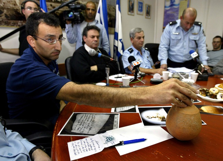 Israel's archaeological authorities investigator, Amir Ganor displays a jar dated from the 8th century B.C. with forged scripts during a press conference in the police headquarters in Jerusalem on Wednesday.