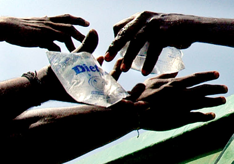 Survivors receive packets of drinking water at a relief camp in Madras