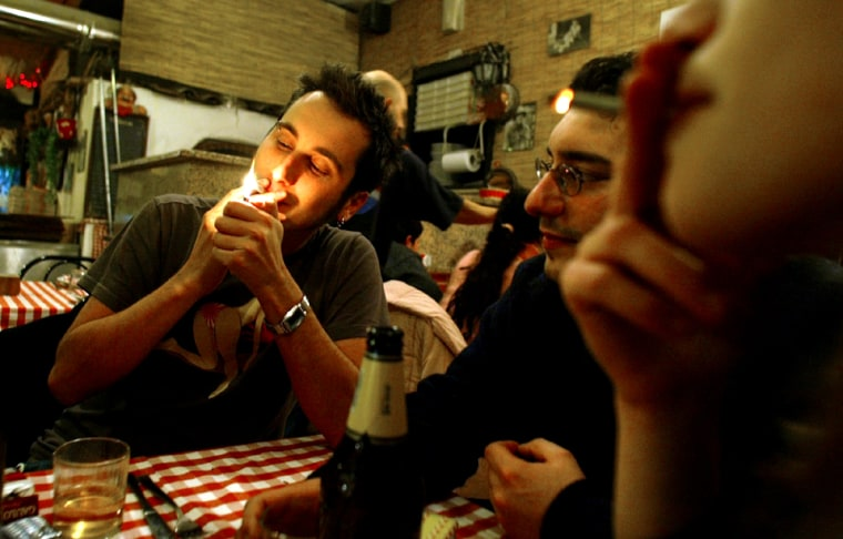 Customers smoke cigarettes in a restaurant in Rome