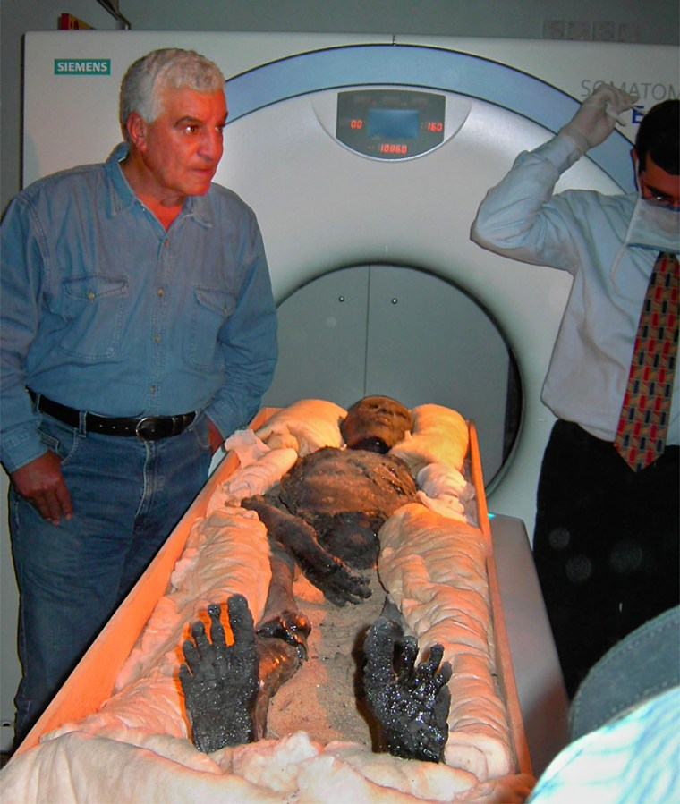 The 3,300-year-old mummy of the ancient King Tutankhamun lies exposed on a CT machine in Luxor, Egypt on Wednesday as Egyptian antiquities chief Zahi Hawass, left, looks on.