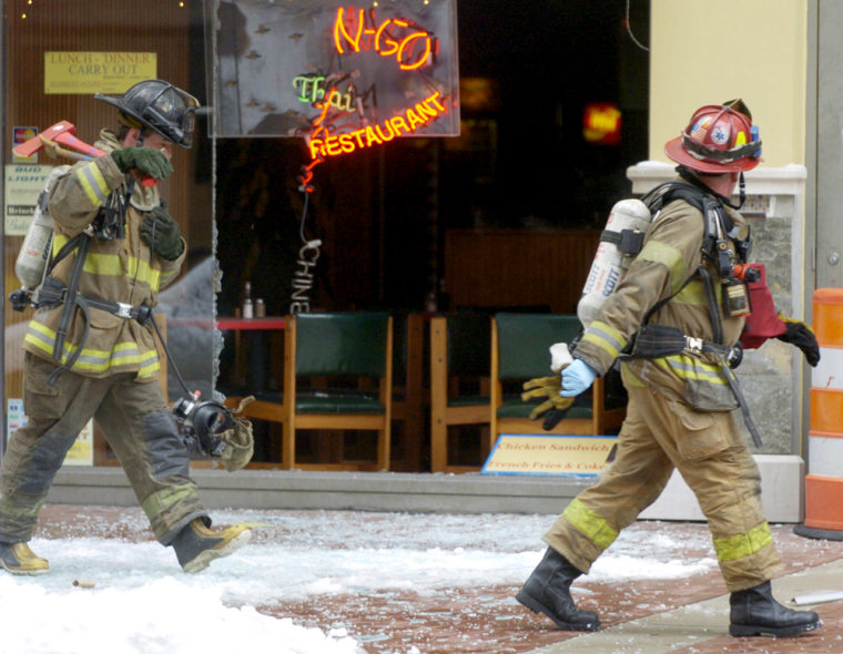 Firefighters walk past the blown-out windows of the Wok-N-Go restaurant in downtown Indianapolis on Saturday. An underground explosion forced authorities to evacuate dozens of residents from a nearby condominium.