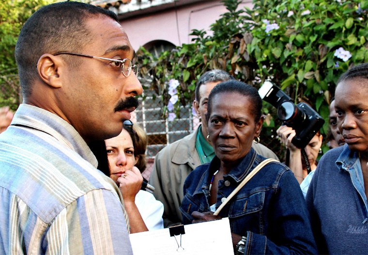 An unidentified member of Cuban State Security, left, establishes a list of the family members allowed to enter the courthouse in Havana, Cuba, on Wednesday.Twenty-three men went on trial in the violent occupation of the Mexican Embassy in Cuba three years ago.