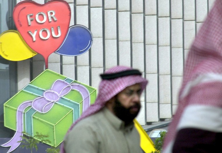 A Saudi manwalks past a store with a rare big heart sign on Friday in Riyadh, Saudi Arabia.