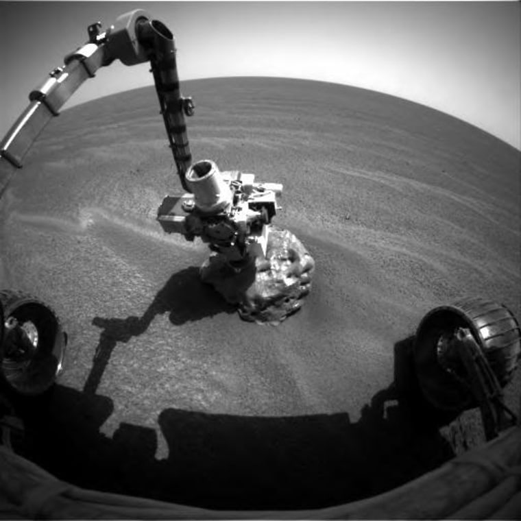 "The Opportunity rover extends its instrument-laden robotic arm to take a close look at ""Heat Shield Rock,"" which could be a meteorite on the Martian surface."