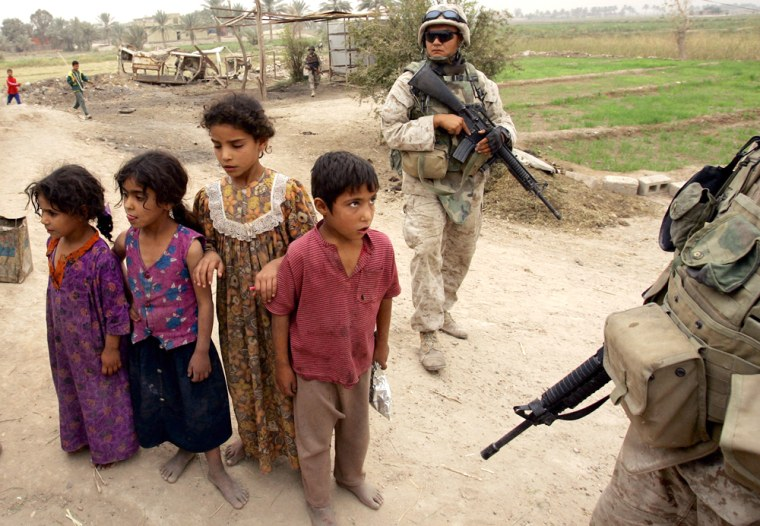 Iraqi children look on as U.S. Marinessearch the area outside Fallujah last October.