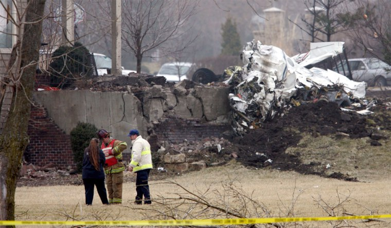 Emergency workers talk near the site of a twin-engine plane crash in an affluent neighborhood of Overland Park, Kan., on Friday.