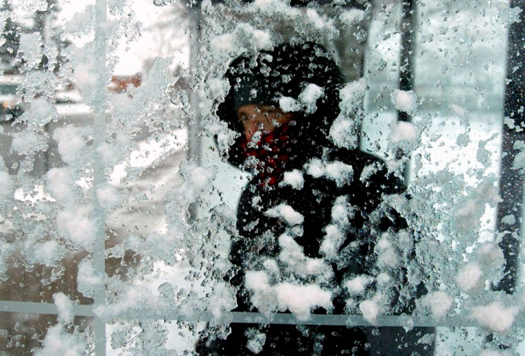 A woman peers through a snow-covered bus shelter as she waits for her ride on Chicago's north side earlier this month. Winter could get even more depressing on Monday, according to a British researcher.