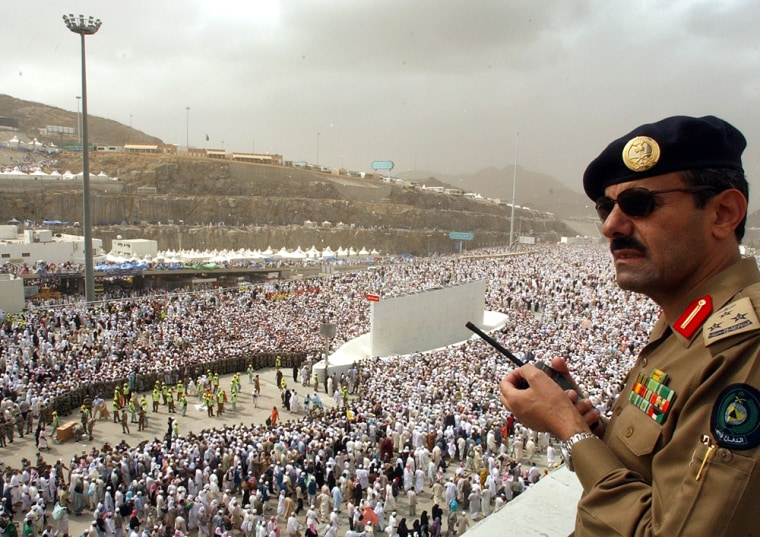 A Saudi police officer stands watching millions of pilgrims crowd to throw stones at pillars representing the devil in Mina, outside of Mecca, Saudi Arabia, Saturday.