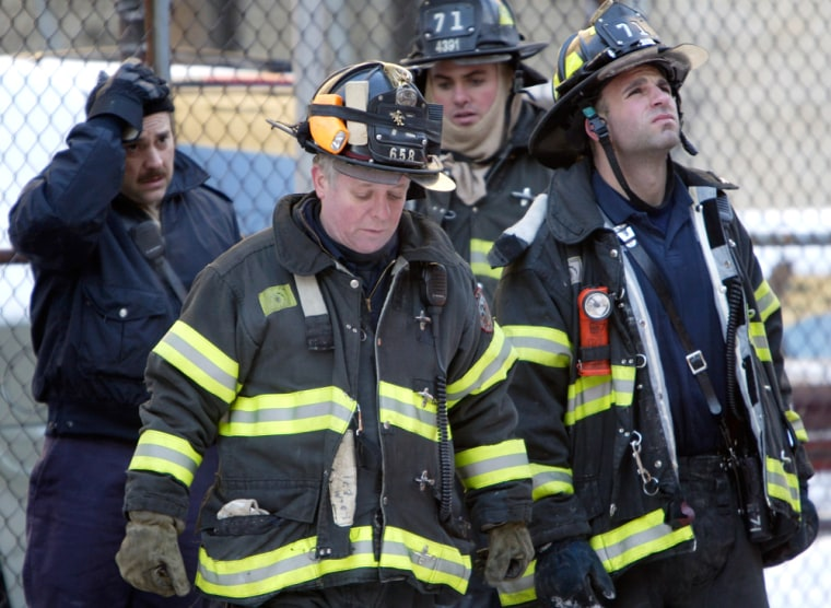 New York City fire crews look up at the building where two firemen were killed and four others badly injured Sunday in an early morning fire in the Bronx.