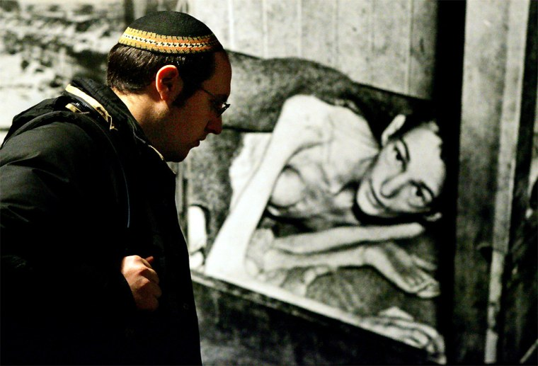 A visitorlooks at images of Holocaust survivors that were taken on liberation day at the Auschwitz-Birkenau concentration campon display at the Yad Vashem Holocaust Memorial in Jerusalem on Monday.