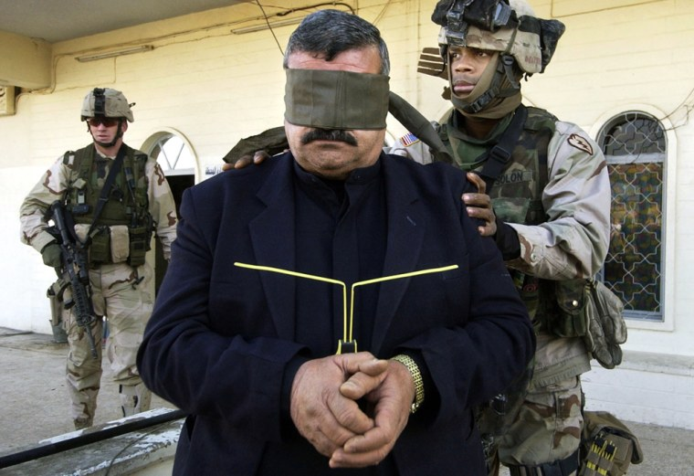 An Iraqi man is detained by U.S. soldiers during a weapons raid at a gas station in Mosul onTuesday.