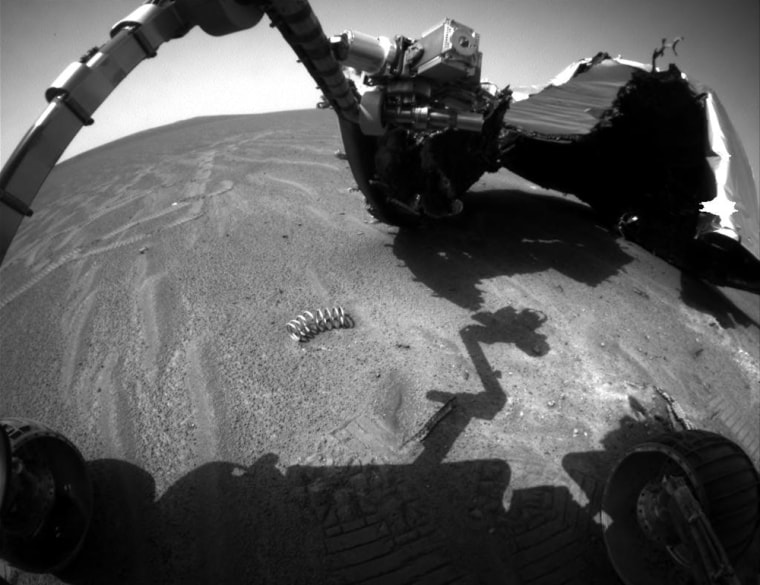 Opportunity's robotic arm hangs out over debris from its own heat shield — including a stray spring — ina picture taken by the Mars rover's navigation camera.