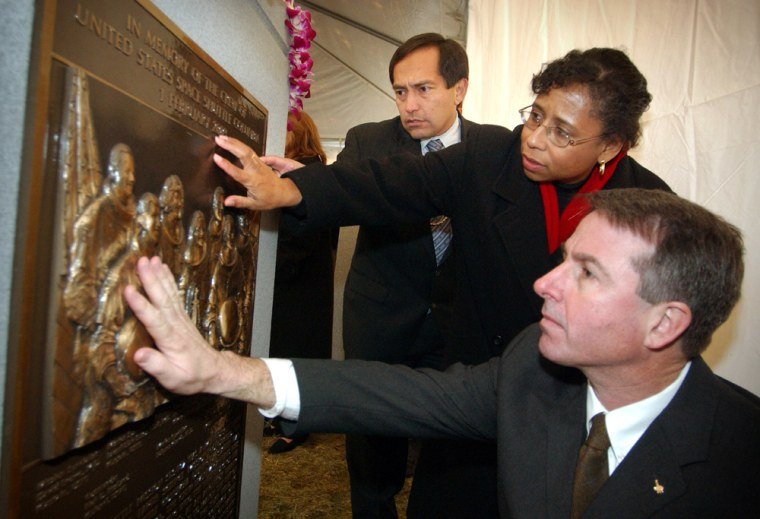 Sandy Anderson, the widow of Columbia astronaut Michael Anderson, touchesa memorial for the Columbia's crew at Arlington National Cemetery after its dedication on Feb. 2, 2004. She is flanked by astronaut Carlos Noriega on theleft and astronaut Steve Robinson on theright.