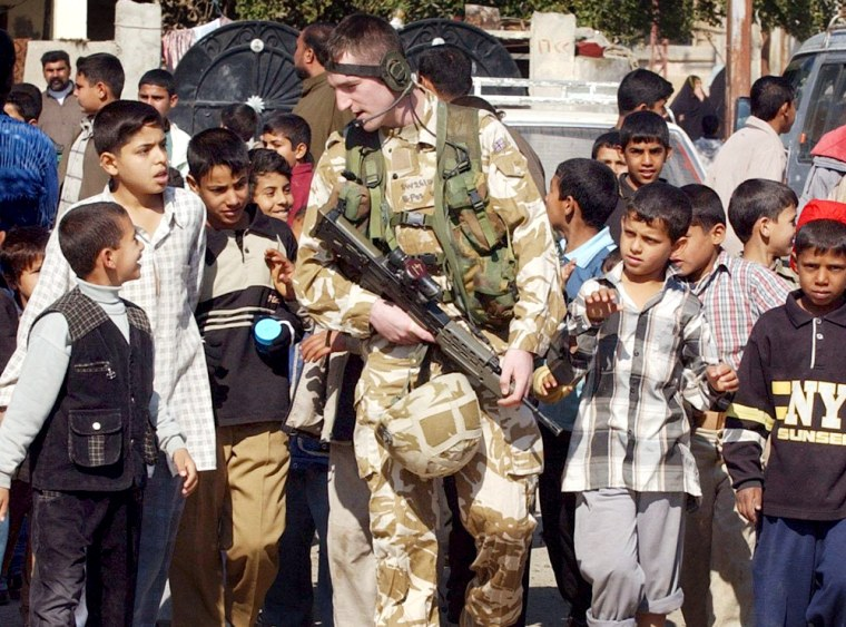 A British soldier walks among Iraqi children in the Hyyaniah area of Basra on Thursday.