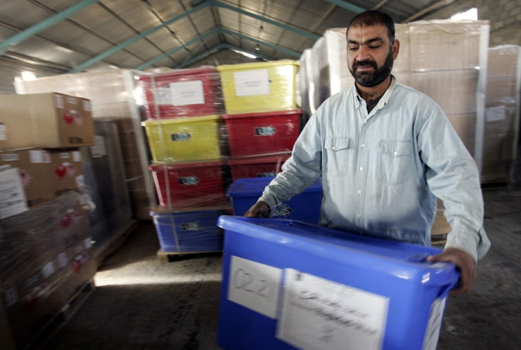 An Iraqi election worker carries a ballot box after their arrival at a warehouse in Hilla, 75 miles south of Baghdad, on Friday.