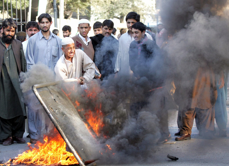 Supporters of a slain Sunni Muslim cleric burn road signs during violence in Karachi