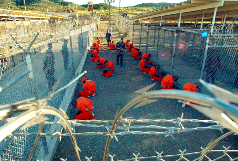 A file photo shows detainees sitting in a holding area watched by military police at Camp X-Ray inside Naval Base Guantanamo Bay, Cuba