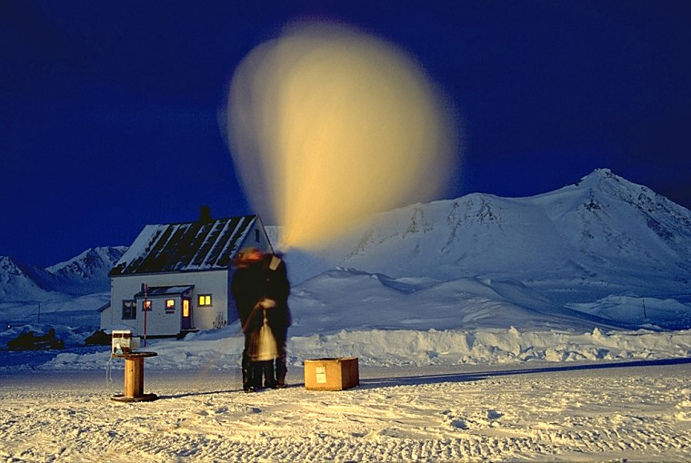 Researchers in Spitzbergen, Norway, prepare to launch a balloon that's hooked up to an ozonesonde, a device that measures ozone layerconditions. The low light created the blurred image of the balloon.