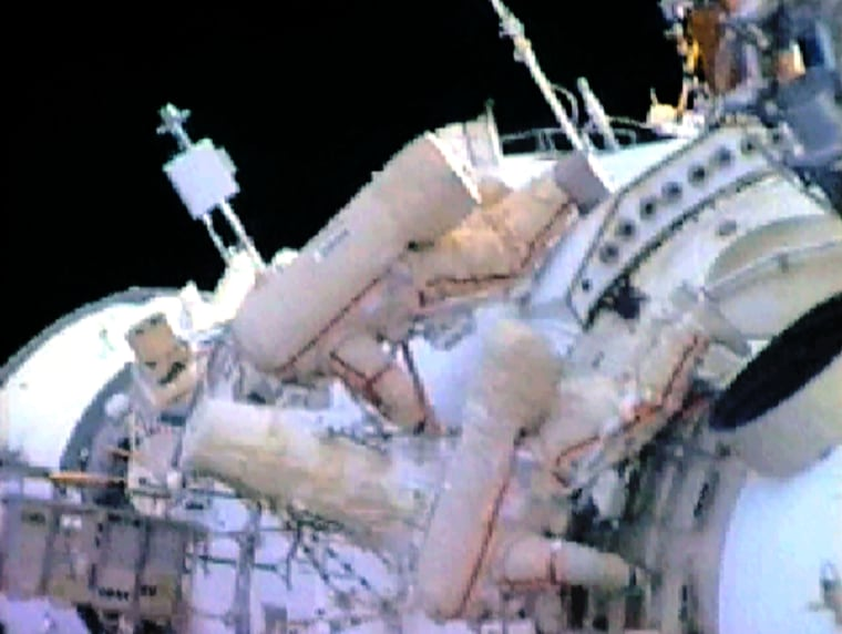 Astronaut and cosmonaut perform space walk at space station