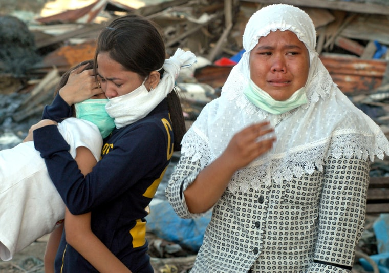 A family in Lampulo, Indonesia, weeps Tuesday after finding the bodies ofrelativeskilled in the tsunami. Recovery is expected to take years.