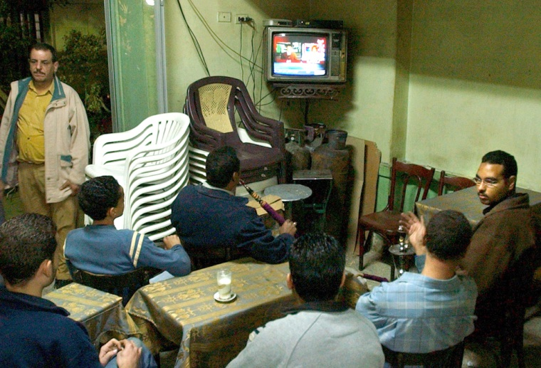 Egyptians watch news about the Iraqi election on Al-Arabiya TV in a coffeeshop in downtown Cairo on Sunday.