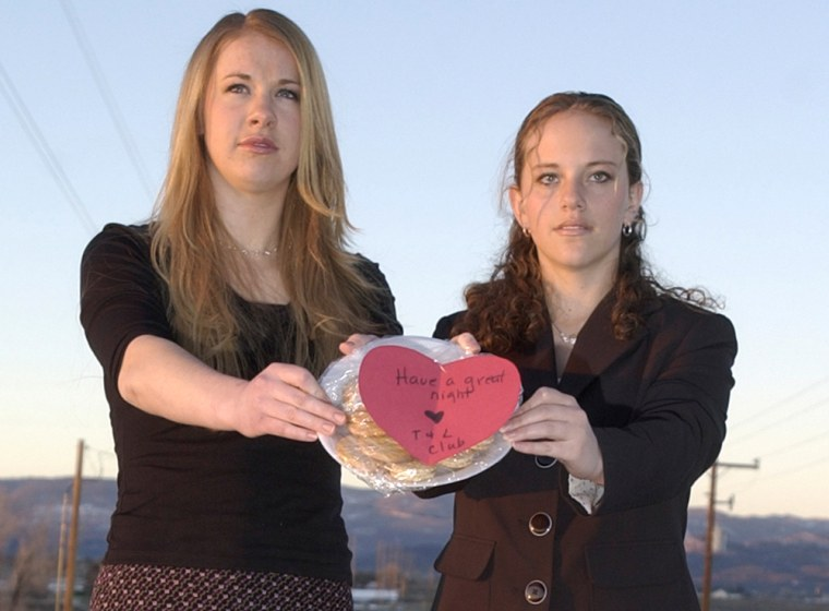 Taylor Ostergaard, left, and Lindsey Zellitti on Thursday display cookies the two made for neighbors last summer.