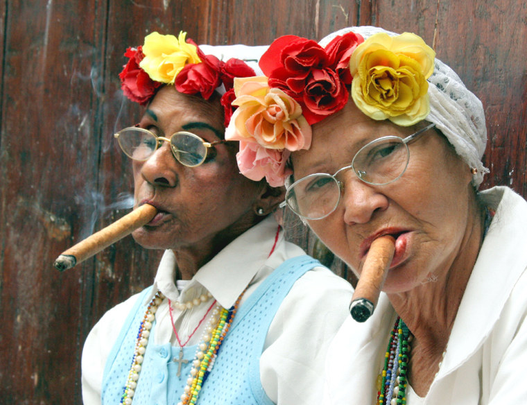 Mercedes Martinez, left, 72, and Josefa Gamet, 62, make money posing for photos for foreign tourists in Old Havana, Cuba. Beginning Monday, Cuba began an island-wide ban on smoking in public places.