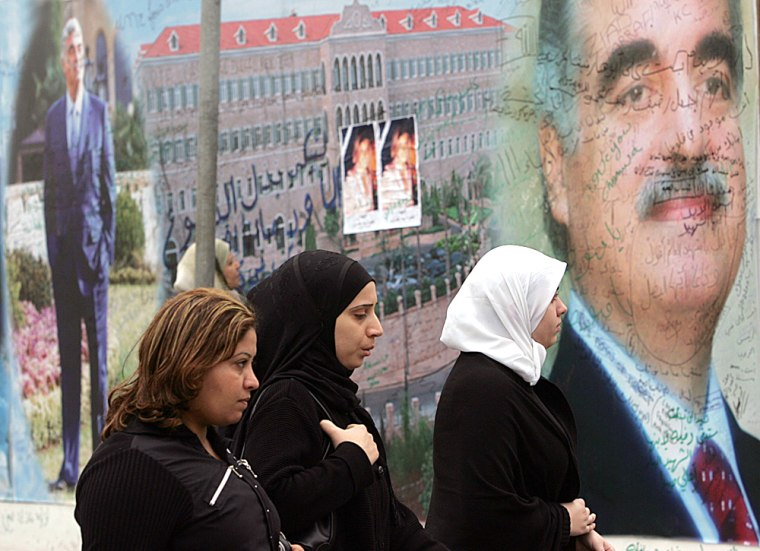 Lebanese women pass a mural of Lebanon's slain former prime minister Rafik Hariri covered with poems and condolences from wellwishers near his grave in Beirut, on Sunday. At his funeral, Christians, Muslims and Druse came together in a vivid manifestation of unity rare in Lebanon's violent, sectarian-charged history.