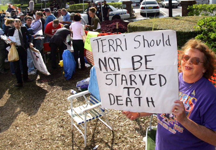 A supporter of  brain-damaged Florida woman Terri Schiavo holds poster in front of the the Woodside Hospice in Florida